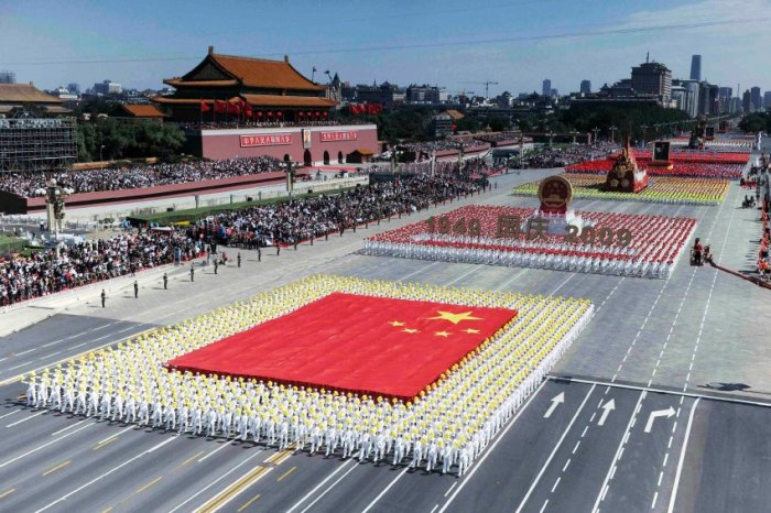 People in formation carry the national flag and national emblem during a parade in central Beijing